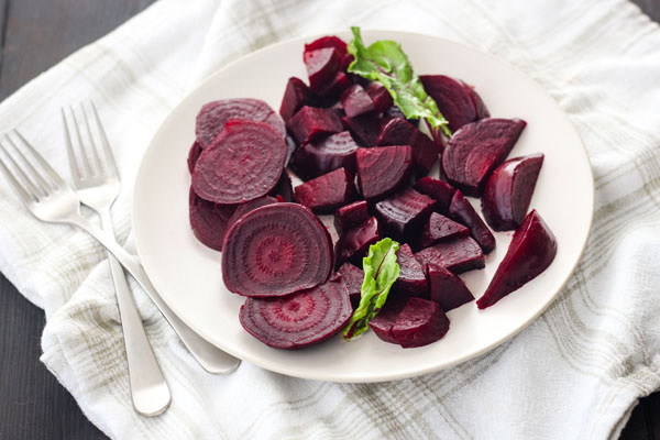 Instant pot mini cooked beets on a white plate.
