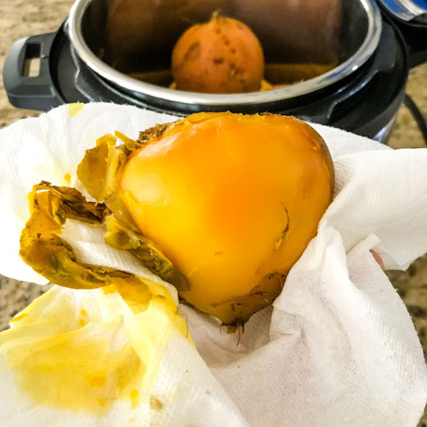 Instant pot cooked golden beet in a paper towel with skin rubbed off.