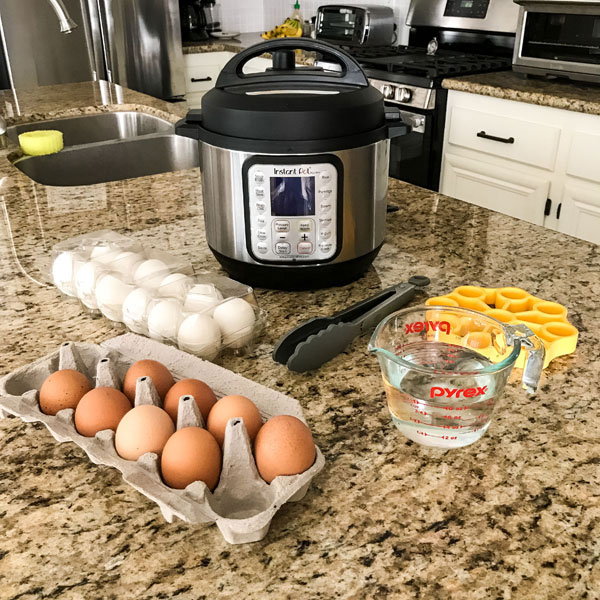 Instant pot mini with accessories and eggs on a kitchen counter.