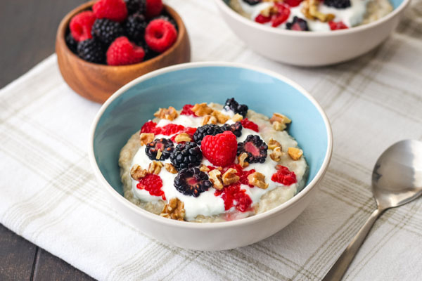 Oatmeal in a blue bowl with a small wooden bowl of berries.