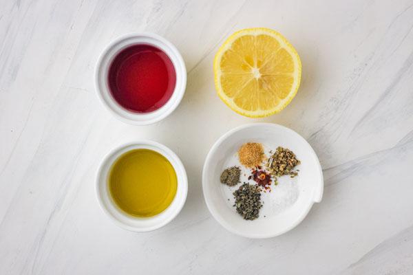 Small ramekins of oil, vinegar, seasonings, and half a lemon.