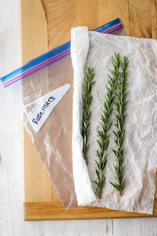 "Rosemary on a damp paper towel next to a plastic bag with the words ""rosemary"" written on it."