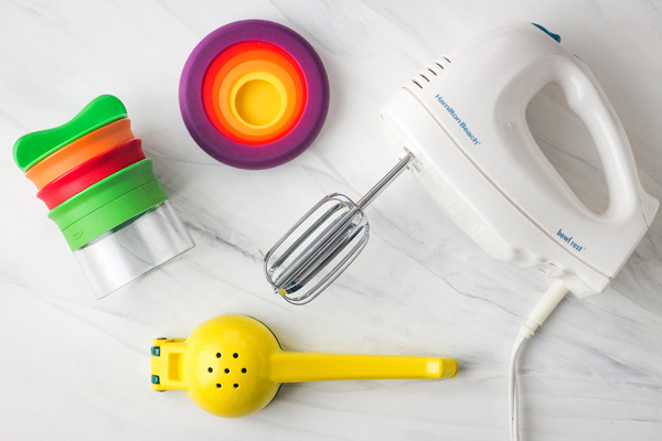 Hand mixer, handheld vegetable spiralizer, and yellow citrus juicer.