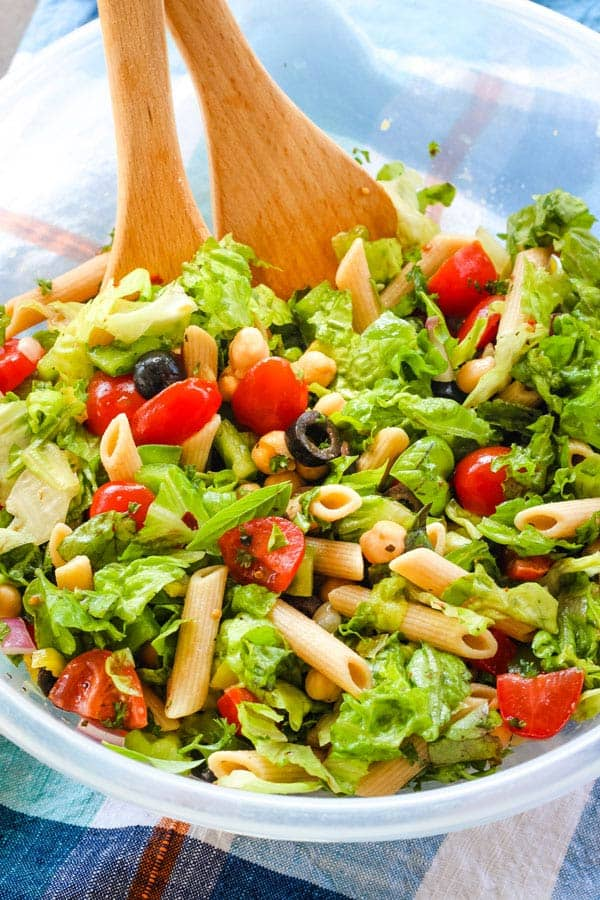 Large plastic bowl of salad with wooden spoons.