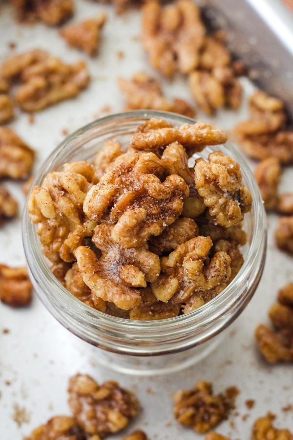 Overhead view of sparkly cinnamon walnuts in a glass mason jar.
