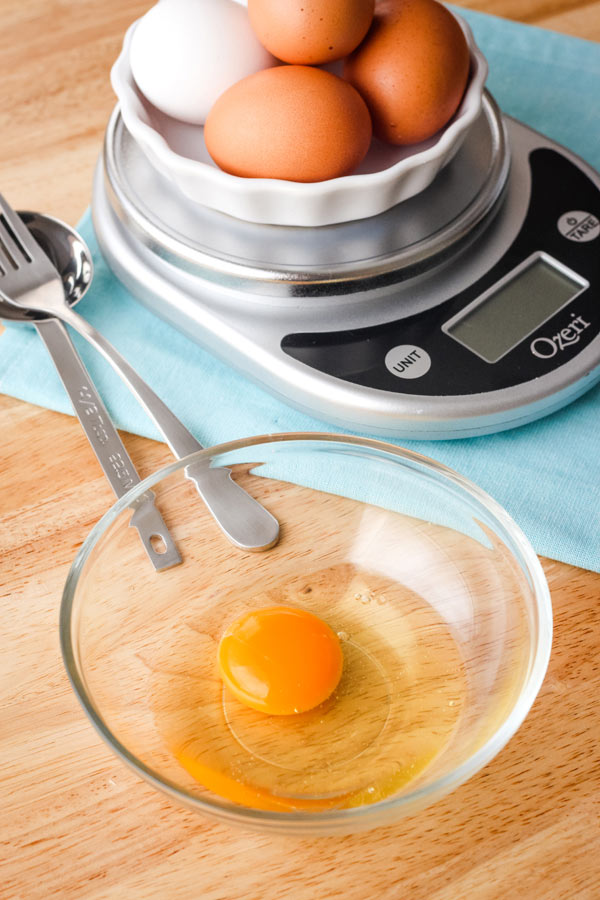 An egg in a bowl in front a scale, measuring spoon, and fork.