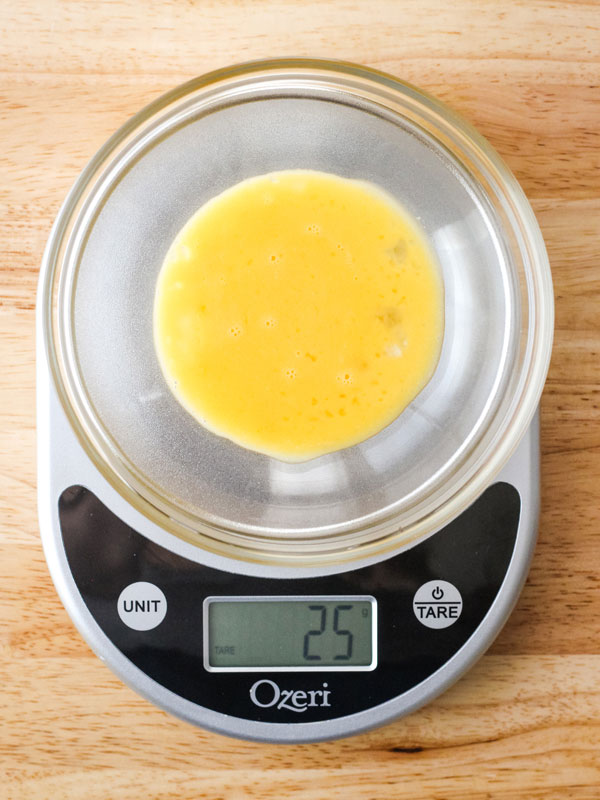 Beaten egg in a bowl on a digital scale with 25 grams displayed on the screen.