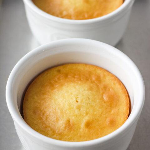 Yellow cake in two white ramekins on a metal sheet pan.
