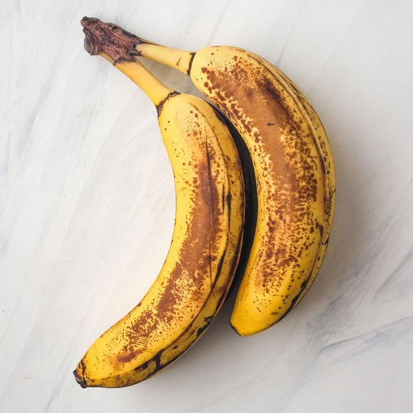 Overripe browned bananas on a white table.