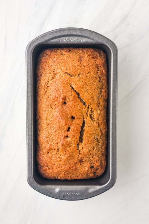 Overhead view of banana bread in a mini metal loaf pan.