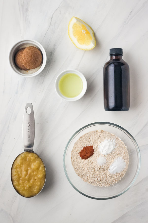A small bowl with flour and spices, mashed banana in a measuring cup and other ingredients on a white table.