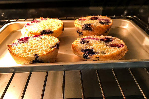 Muffin halves on a small baking sheet cooking inside a toaster oven.