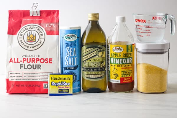 Bag of flour, yeast packet, jars of salt, oil, vinegar and cornmeal on a table.