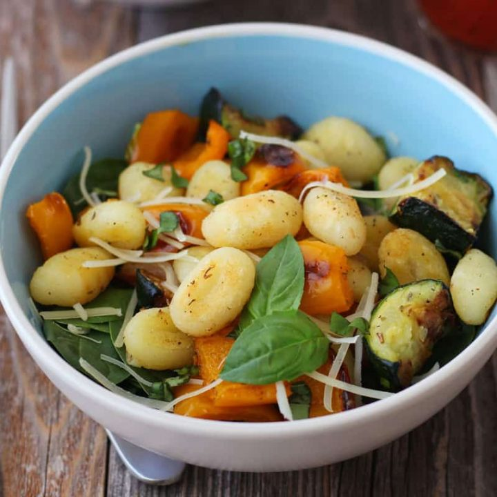 Closeup of roasted vegetables and gnocchi in a bowl on a wooden table.