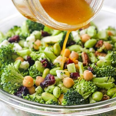 Hand pouring dressing from a mason jar over a broccoli salad.