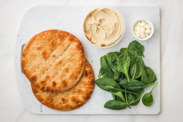 Pita breads, spinach, hummus and feta cheese on a cutting board.