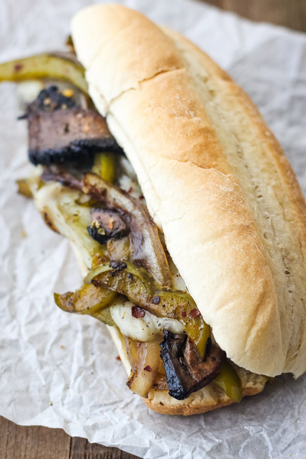 Portobello Mushroom Sandwich with bell peppers, onions and cheese on a piece of white parchment paper.