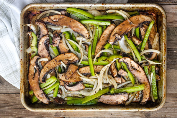 Marinaded mushrooms, peppers, and onions on a sheet pan.