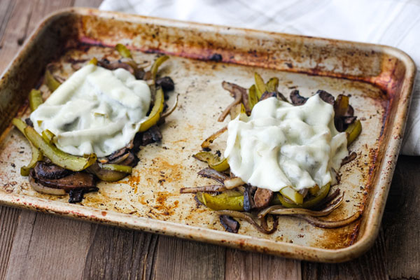 Two piles of roasted vegetables with cheese melted on a sheet pan.