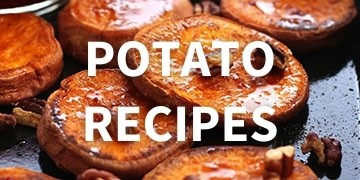 Cooked sweet potato slices on a dark sheet pan.