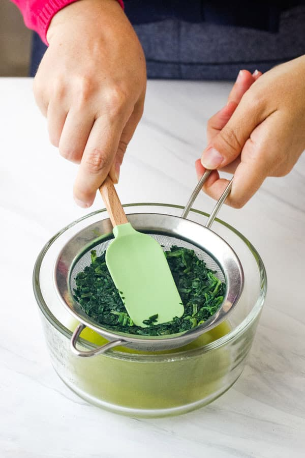 Green liquid in a glass bowl below collecting below spinach pressed in a colander.