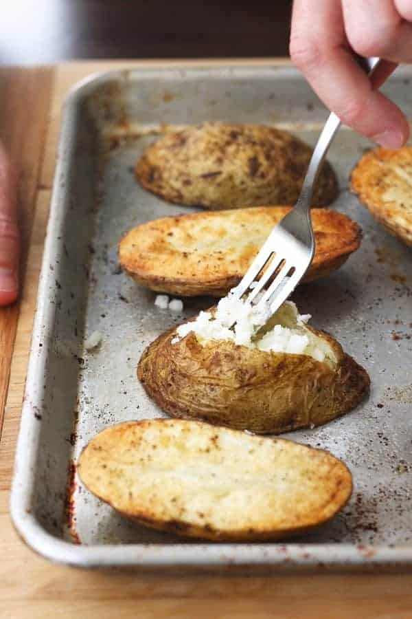 Quick baked potatoes sliced open and fluffed with a fork on a baking sheet