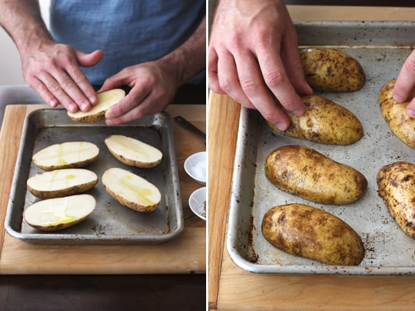 Potato halves rubbed with oil on a baking sheet.