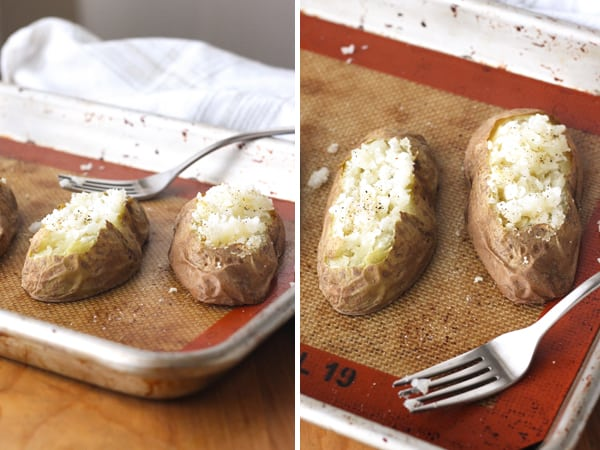 Baked potato halves fluffed with a fork on a silpat lined baking sheet.
