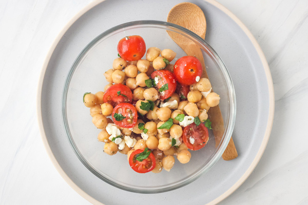 Chickpeas and tomatoes in a glass bowl next to a wooden spoon.