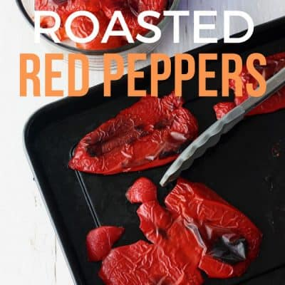 Roasted red peppers on a black toaster oven pan.