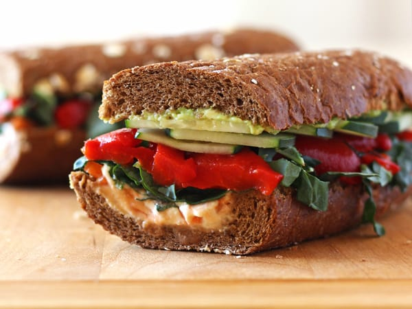 Roasted Red Pepper Hummus Sandwich on a wooden cutting board.