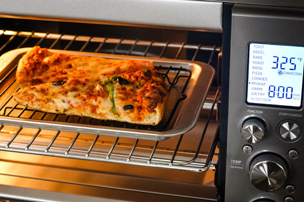 Pizza slices on a rack and pan inside of a toaster oven.