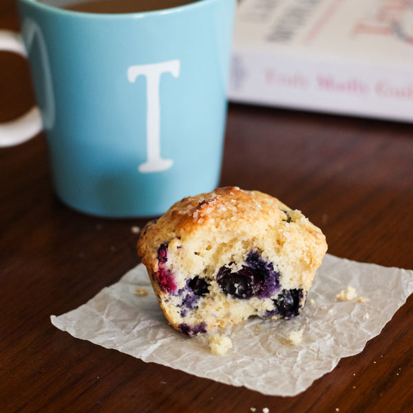 A blueberry muffin, light blue coffee mug and book on a table.