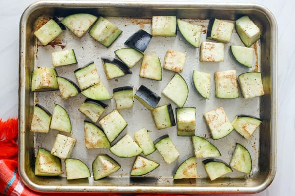 Overhead view of cut eggplant on rimmed sheet pan.
