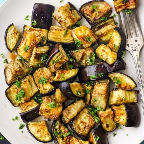 Roasted eggplant on a plate with fork stamped with veg out text.