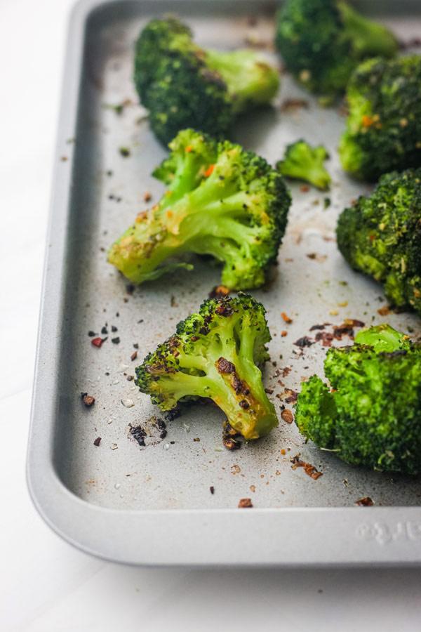 Cooked broccoli on a small metal sheet pan.