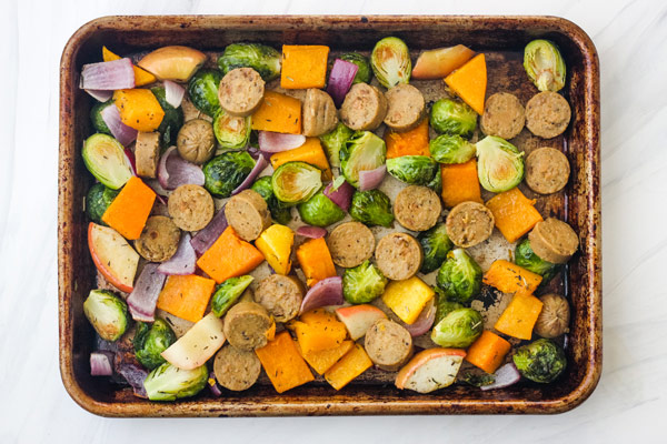 A quarter sheet pan with vegetarian sausage and par-roasted vegetables.