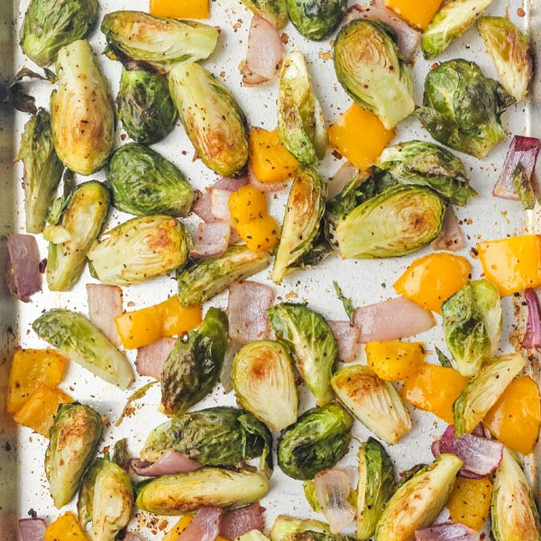 Roasted brussels sprouts, yellow bell pepper, and red onion on a sheet pan.