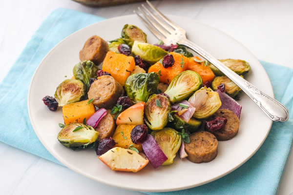 Roasted vegetables and vegan sausage piled on a white plate with a fork.
