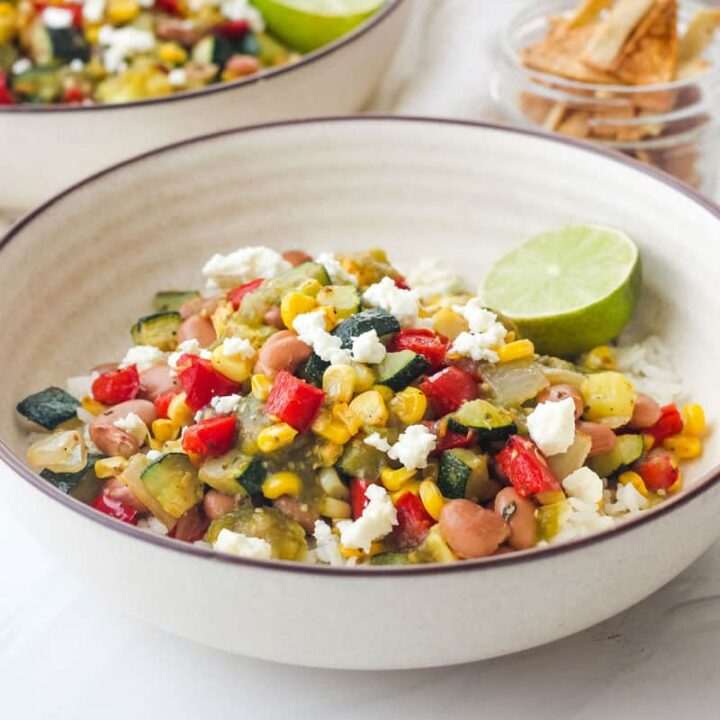 Bowl of rice topped with salsa and colorful roasted vegetables.