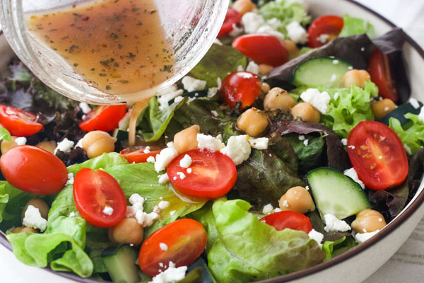 Italian dressing pouring from a mason jar onto a green salad with tomatoes and feta.