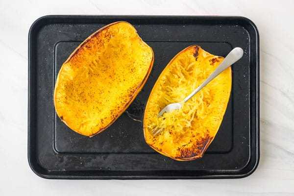 Fork scraping cooked spaghetti squash into strands.
