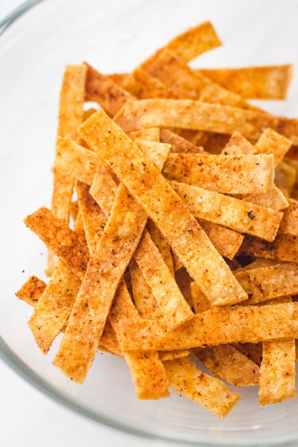 Taco seasoning coated tortilla strips in a glass bowl.