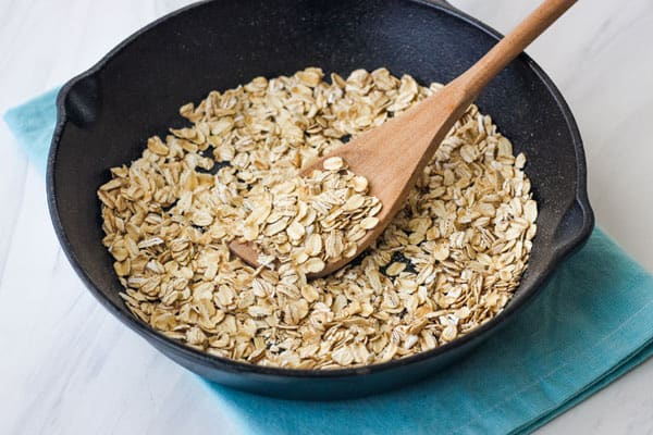 Cast iron skillet with spoon stirring toasted oats.