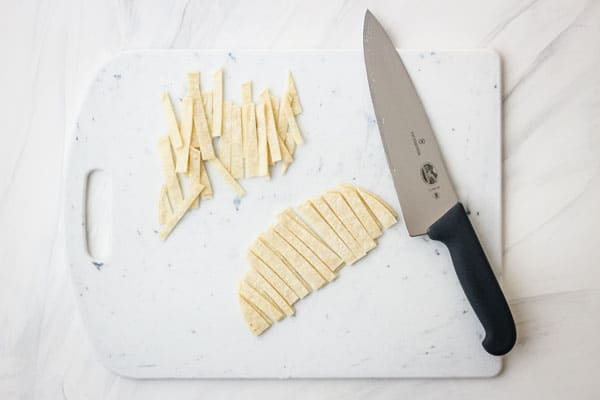 Cutting board with sliced tortillas.