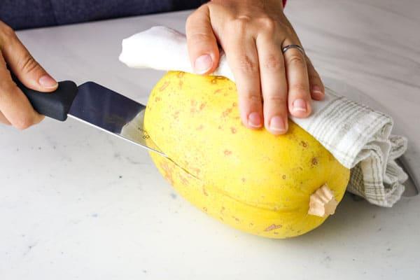 Person slicing into the side of a spaghetti squash.