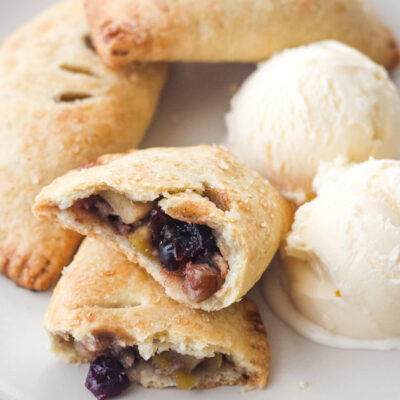 Hand pies on a plate with scoops of vanilla ice cream.