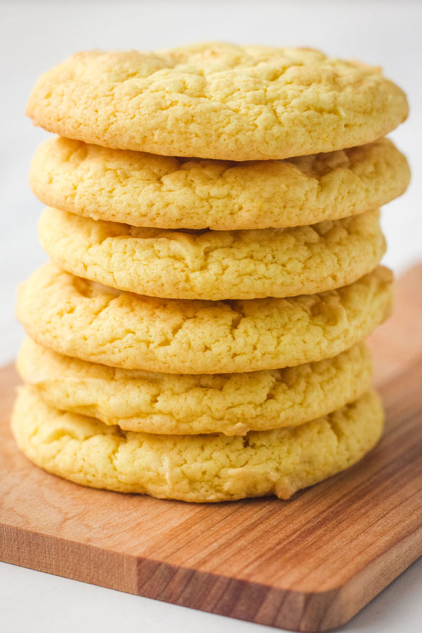 Stack of cookies on a wooden cutting board.