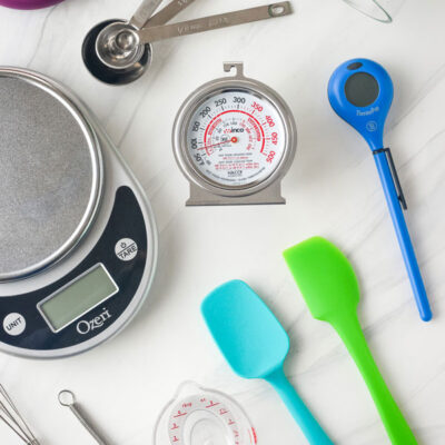 Digital scale, oven thermometer, mini rubber spatula, and more small kitchen tools.