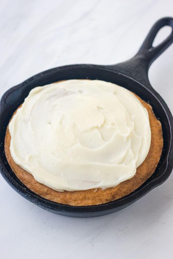 A mini pumpkin skillet cake topped with a rich cream cheese frosting on a marble background.